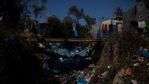Una persona refugiada cruza un puente sobre un montón de basura en el campo de Moria, en la isla de Lesbos.