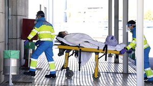 Enfermeros trasladan a una mujer mayor concoronavirus a Urgencias del Hospital Puerta de Hierro en Majadahonda, Madrid.