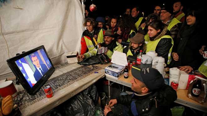 Macron anuncia una subida de 100 euros del salario mínimo para aplacar las protestas de los 'chalecos amarillos'. En la foto, un grupo de ellosescuchael discurso de Macron, ellunes en La Ciotat, cerca de Marsella.