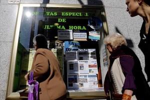 Varias personasmiran el escaparate de una agencia de viajes, en Madrid.