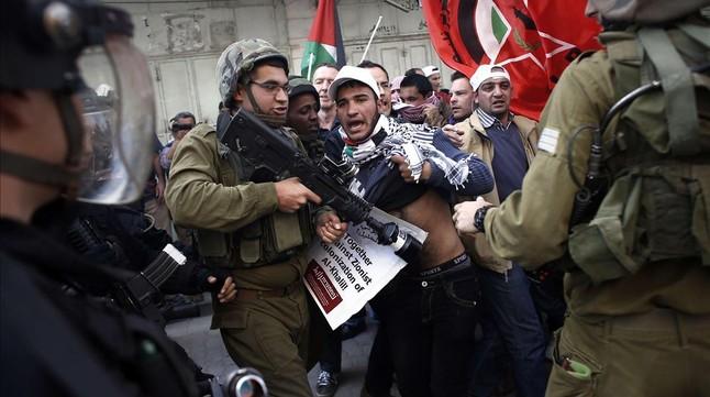 Palestinos y soldados israelís forcejean en el centro de Hebrón, este viernes.