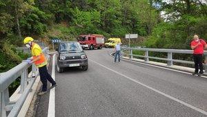 Un sanitario observa desde el puente el coche que cayó al río Brugent.