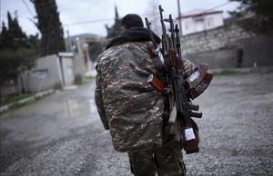 Un soldado de las fuerzas de antodefensa de Nagorno-Karabaj cargado de fusiles antes de firmarse el acuerdo de alto el fuego.