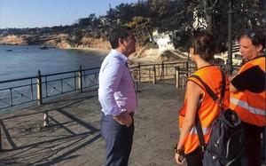 Tsipras habla con dos miembros de protección civil en Mati.