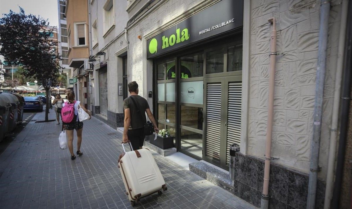 Un turista con maletas, en la calle Onze de Setembre de L'Hospitalet.