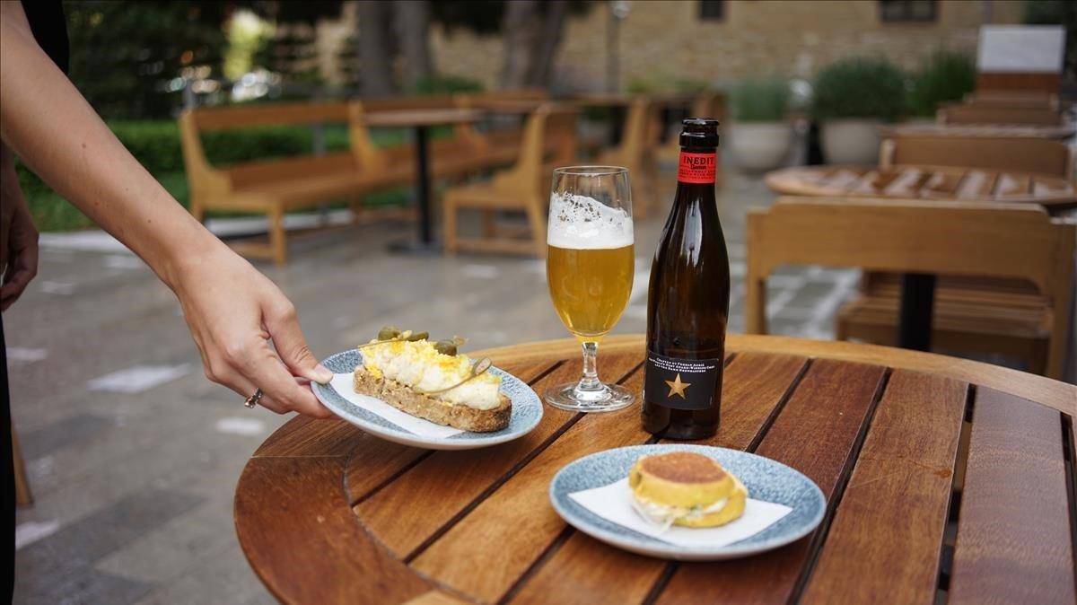 Una camarera sirve dos tapas y una cerveza en una terraza en una imagen de archivo