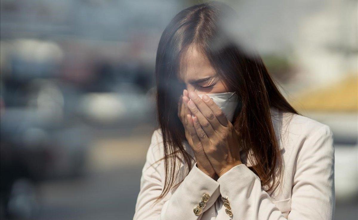 Una mujer con mascarilla estornuda.