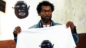 Mouhamed, vendedor senegalés, muestra una de las prendas de la marca Top Manta.