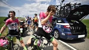 Un ciclista se echa agua en los ojos.