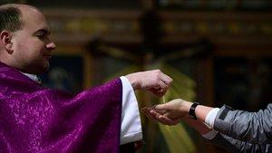 Un sacerdote coloca una hostia en la mano de un feligrés.