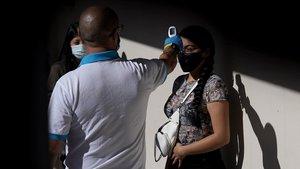 Un sanitario toma la temperatura a una persona antes de hacerse la prueba PCR.