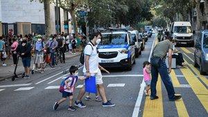 Padres llevando a sus hijos a la escuela en el primer día de clase.