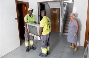 Dos trabajadores de Alencop recogen un televisor en casa de Anastasia, en el barrio del Besòs.