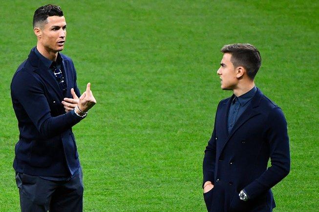 Cristiano Ronaldo (i) charla con Paulo Dybala en sobre el césped del Metropolitano.