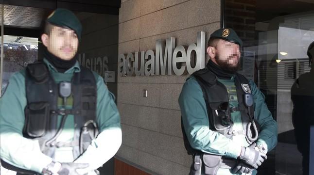 Agentes de la Guardia Civil custodian la sede de la empresa públicaAguas de las Cuencas Mediterráneas (Acuamed), en Madrid, durante el registro de las dependencias.