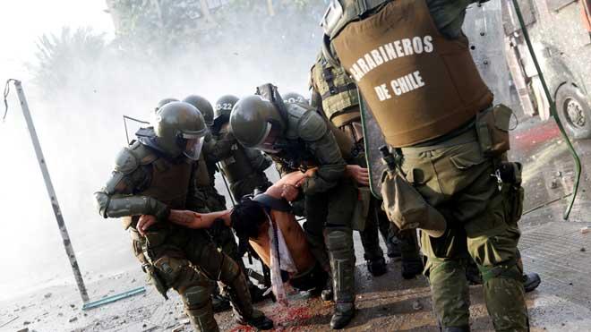 Chile, en ruta hacia una nueva Constitución, por la paz y por otro modelo de país. En la foto, un herido es trasladado por las fuerzas de seguridad durante las protestas en Santiago.