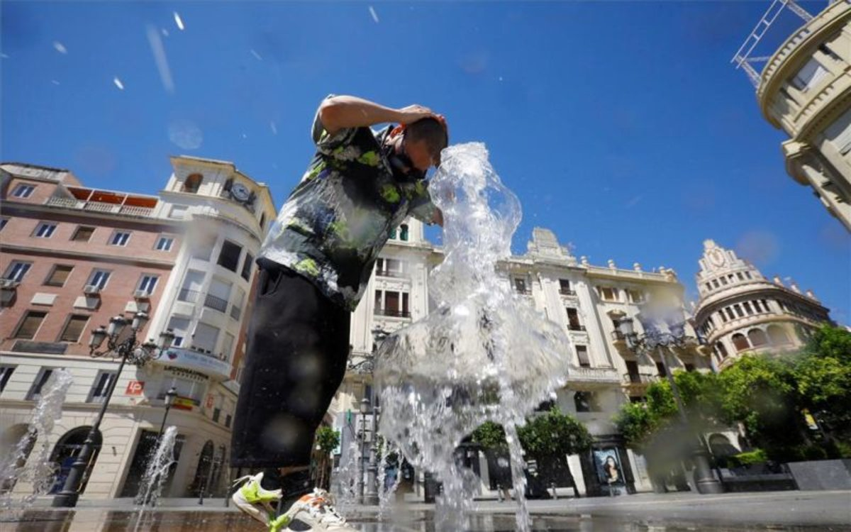 Un hombre se refresca en una fuente por las altas temperaturas.
