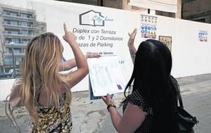 La comercial de una agencia inmobiliaria atiende a una potencial compradora de pisos en el Poblenou.