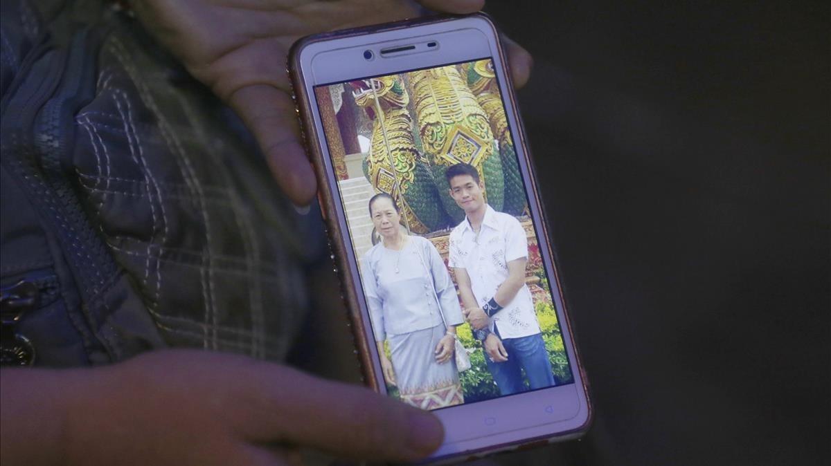 La tia de Ekapol Chanthawong muestra una foto en el móvildel entrenador en la que aparace junto a su abuela.