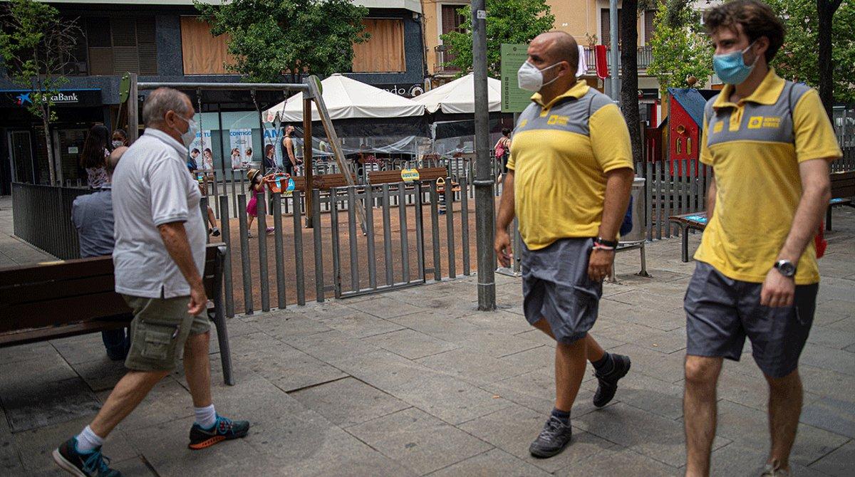 Dos agentes cívicos vigilan el cumplimiento de las medidas anticovid en la plaza Espanyola del barrio de la Torrassa, enL'Hospitalet, este martes 14 de julio.