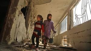 Dos niñas sirias recorren su escuela, destrozada el día anterior por los ataques áereos de la aviación gubernamental, en la sitiada ciudad de Saqba (Guta Oriental), el 9 de noviembre.