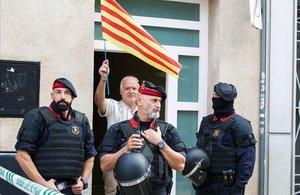 Un hombre con una 'senyera', junto a unos agentes en la operación contra los CDR en Sabadell.