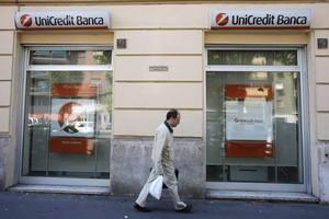 Un home passa davant d'una oficina d'Unicredit a Milà.