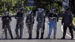 Integrantes del Cuerpo de Policía Nacional Bolivariana (CPNB) vigilan en una calle durante una manifestación de apoyo a un grupo de militares sublevados, el 6 de agosto.