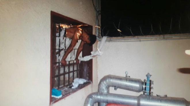 Intenta escapar de la prisión y queda atrapado en la ventana de la celda.