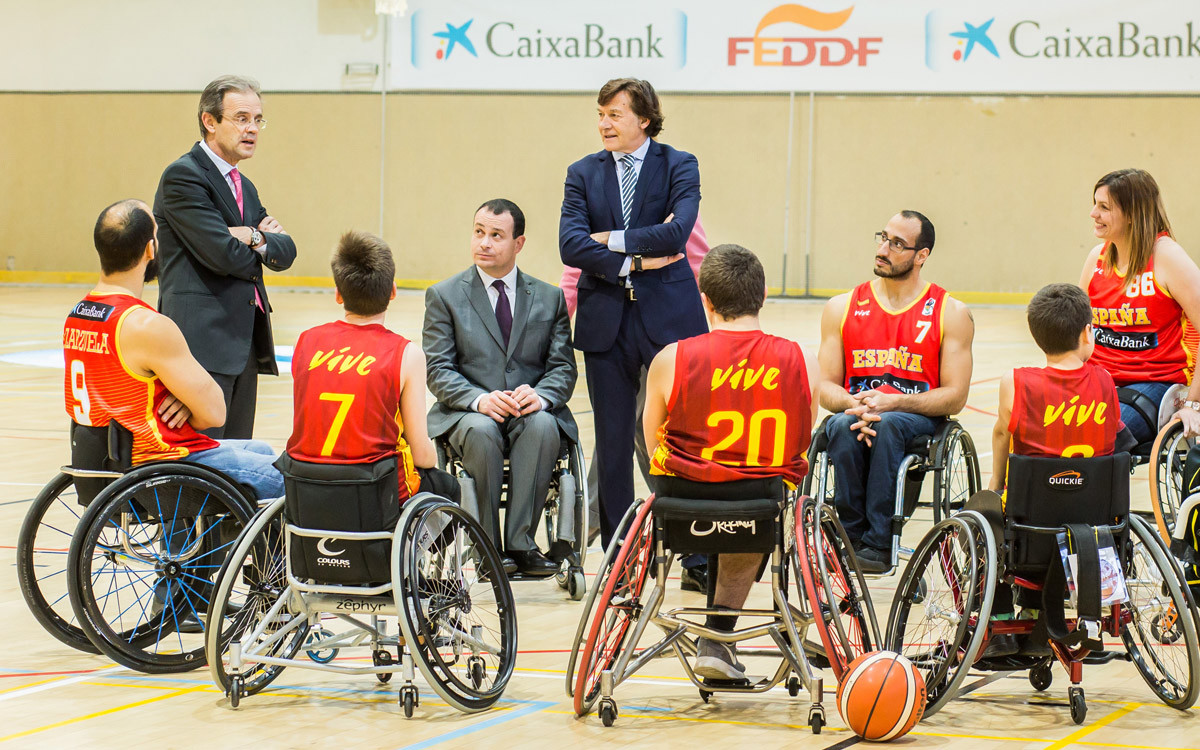 Jordi Gual, José Alberto Álvarez y José Ramón Lete (de traje, de izquierda a derecha) conversan con integrantes de la selección española de baloncesto en silla de ruedas.