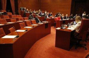 Plano general desde un lateral de las sillas vacías de JxCat, ERC y CUP en la comisión de la Sindicatura de Cuentas.