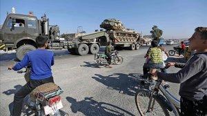 Los niños de Maaret al-Numan, en la provincia de Idlib, en el norte de Siria, observan cómo un vehículo transporta un tanque turco que, según los informes, parte del convoy de vehículos militares se dirige hacia la ciudad de Khan Sheikhun, en el sur de la provincia, el 19 de agosto de 2019