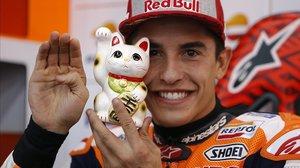 Marc Márquez muestra a su gato de la suerte japonés, al que tiene junto a él en el box del equipo Repsol Honda, en Motegi (Japón).