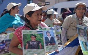 Madres de inmigrantes desaperecidos en México muestran fotos de sus hijos.