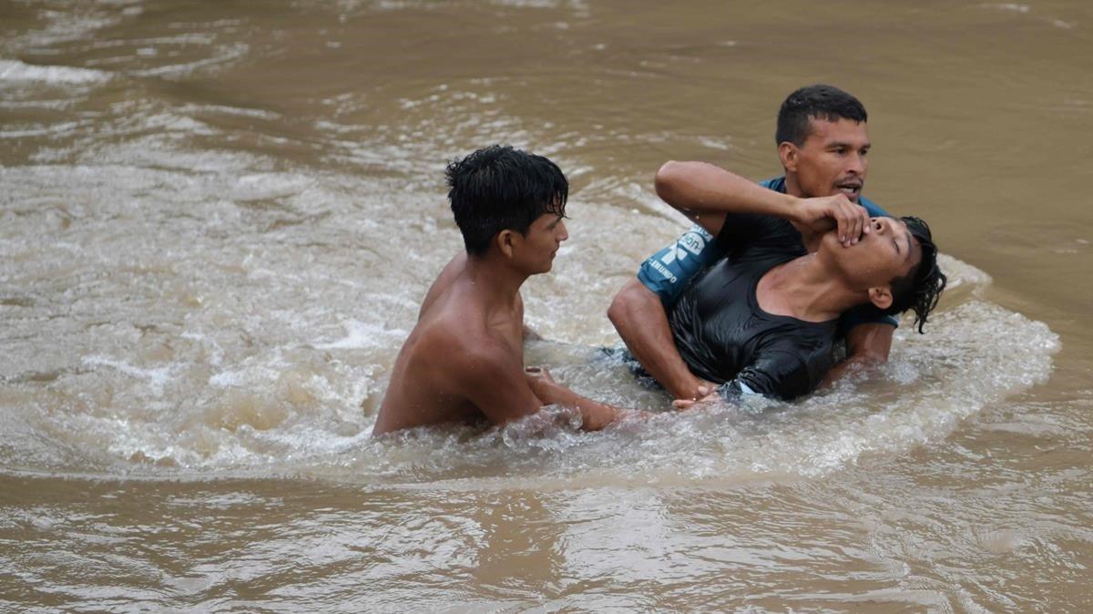 Migrantes hondureños tratan de cruzar el río Goascarán para ingresar en El Salvador de manera clandestina.