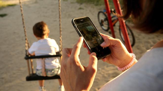 Una madre mira su teléfono móvil mientras su hija juega en el parque.