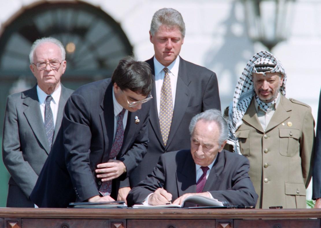 Peres firma los acuerdos de Oslo, observador, de izquierda a derecha, por Isaac Rabin, Bill Clinton y Yasir Arafat, el 13 de septiembre de 1993.
