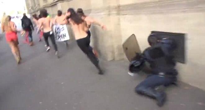 Un policía choca contra la pared al intentar interceptar a una activista de Femen, en París, este lunes.