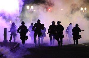 Policías caminan envueltos por gases lacrimógenos en Portland.