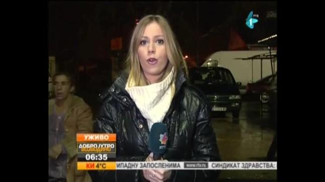 La reportera Tamara Bojic continua el seu directe tot ique un individu li mostra una pistola.