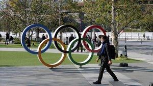Un hombre pasa junto a los aros olímpicos que hay a las afueras del Estadio Olímpico de Tokio.