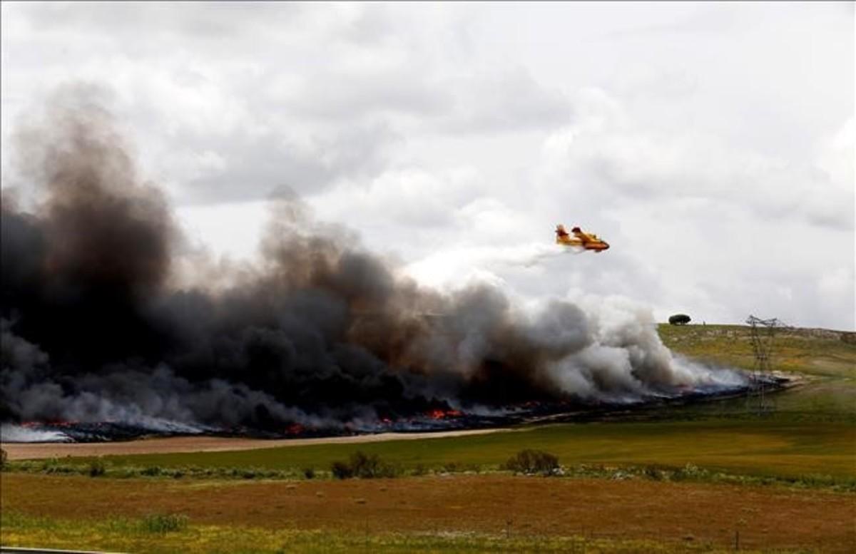 Un hidroavión intenta apagar el fuego declarado esta mañana en el cementerio de neumáticos de Seseña