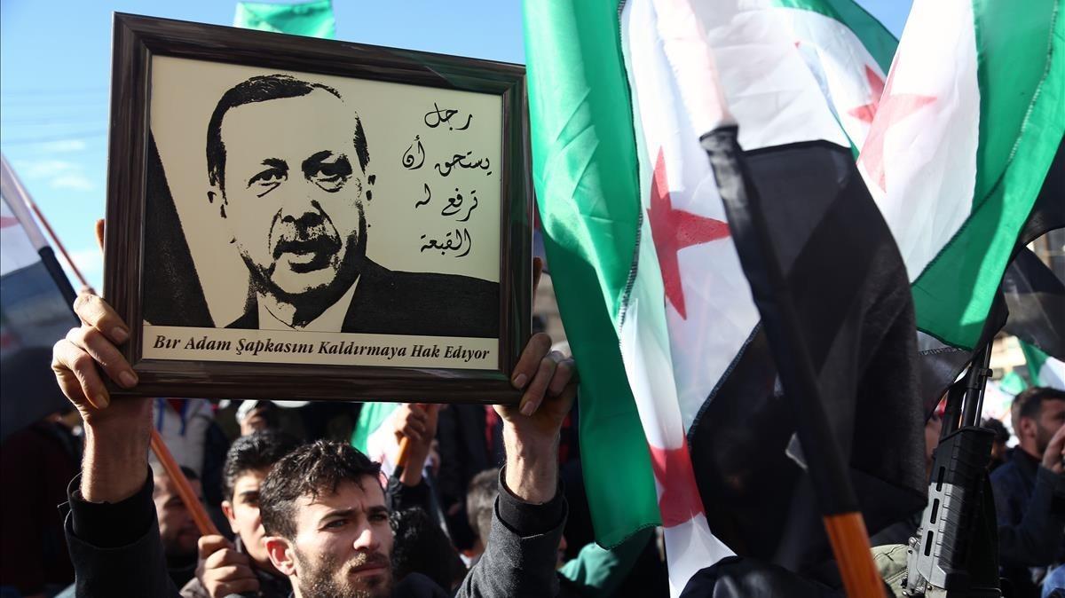 Simpatizantes de los rebeldes sirios levantan un retrato de Erdogan en apoyo de la operación turca contra las milicias kurdas, este viernes en Azaz (Siria).