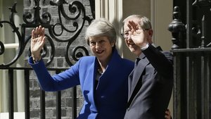 Theresa May junto a su marido Philip May saludan tras abandonar Downing Street.