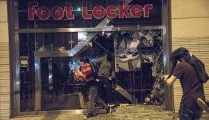 Un hombre sale con cajas de zapatos de la tienda Foot Locker, la noche del sábado