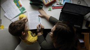 Una mujer ayuda a su hijo a hacer las tareas escolares en su casa de Madrid, el 15 de abril.