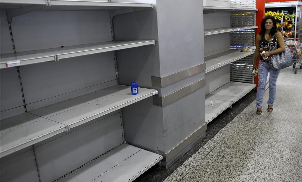 Una mujer pasa junto a unas estanterías vacías en un supermercado en Caracas.