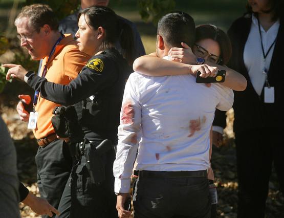 Una pareja se abraza tras el tiroteo en el centro de discapacitados de San Bernardino.