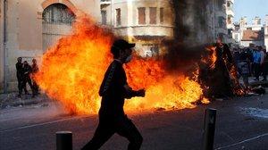 Unos jóvenes queman contenedores de basura en Marsella durante una manifestación contra los planes fiscales del Gobierno francés.