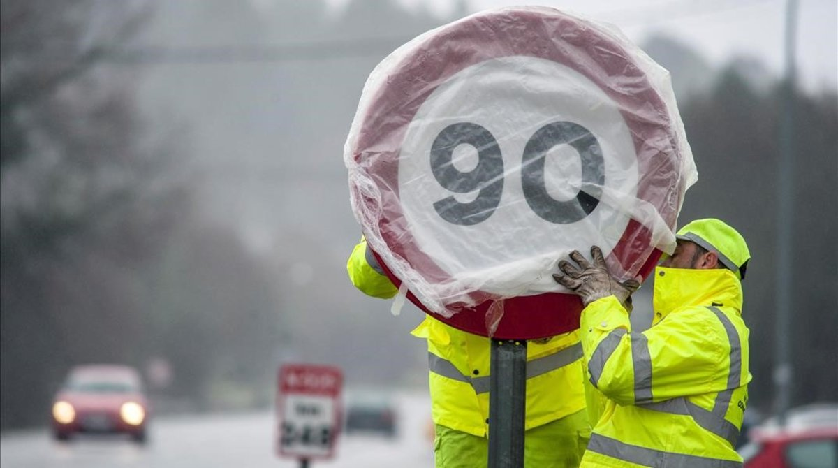 Unos operarios cambiando una señal de 100km/h por una de 90km/h